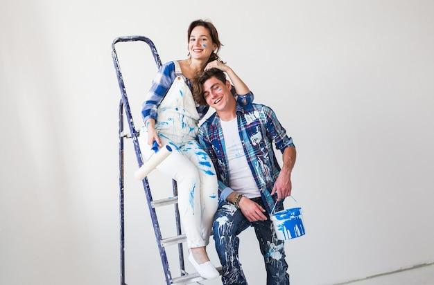 Zabawna młoda kobieta i mężczyzna stojący na drabinie