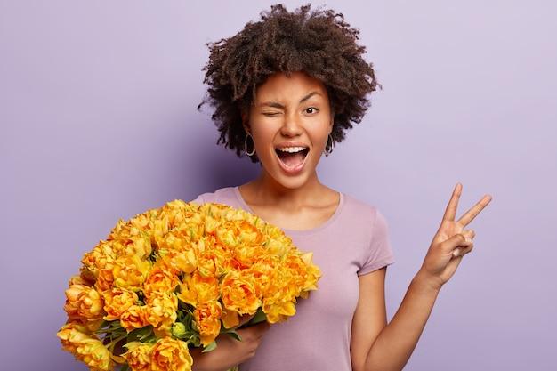 Zabawna młoda kobieta mruga oczami, czyni ręką znak pokoju