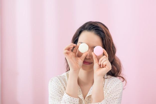Zabawna młoda kobieta trzymająca makaroniki w pobliżu oczu, przed różową ścianą