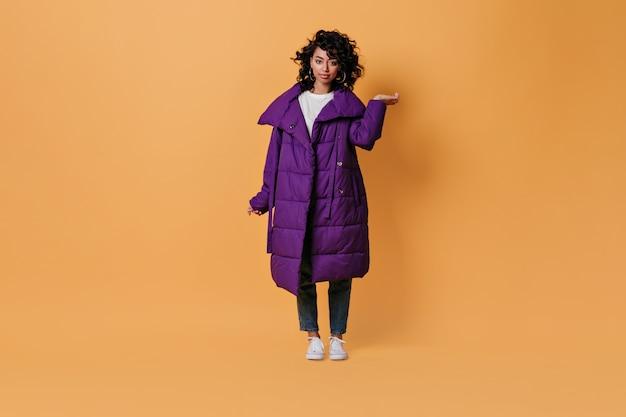 Zabawna młoda kobieta w fioletowej kurtce puchowej patrząc z przodu
