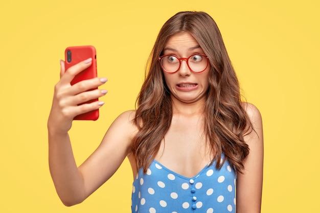 Zabawna młoda kobieta w okularach, pozowanie na żółtej ścianie