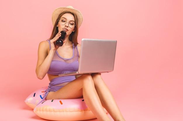 Zabawna młoda kobieta w stroju kąpielowym na białym tle na różowym tle