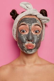 Zabawna młoda kobieta wydyma usta, nakłada maseczkę z glinki na twarz, patrzy bezpośrednio, ma dwie czesane bułeczki, pozuje nago w domu, wypróbowuje nowy produkt kosmetyczny, cieszy się, że ma świeżą, czystą skórę.