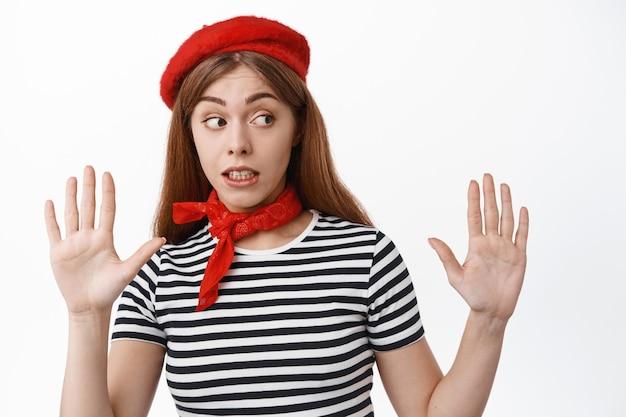 Zabawna młoda kobieta wykonuje pantomimę, mim odchyla się, podnosząc ręce, jakby opierał się o niewidzialną ścianę, stojąc nad białą ścianą