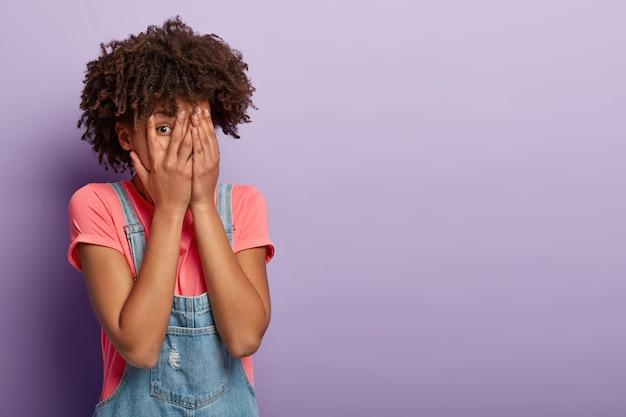 Zabawna młoda kobieta z afro pozowanie w kombinezonie