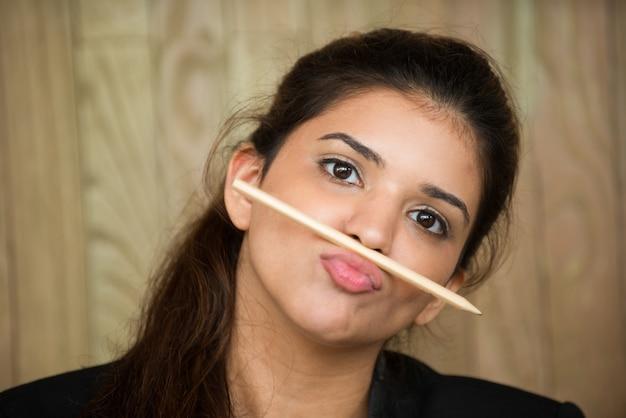 Zabawna młoda kobieta z ołówkiem między wargą i nosem