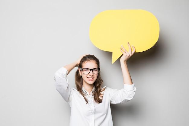 Zabawna młoda ładna dziewczyna studentka trzyma żółte chmury na czacie nad głową na białym tle