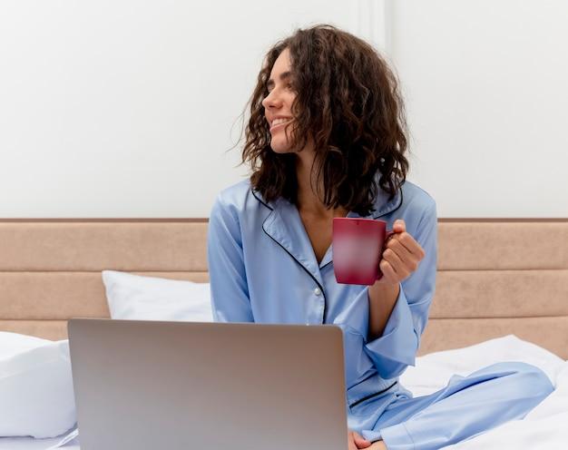 Zabawna młoda piękna kobieta w niebieskiej piżamie siedzi na łóżku z filiżanką kawy, pracując na laptopie, szczęśliwa i pozytywna, patrząc na bok we wnętrzu sypialni na jasnym tle