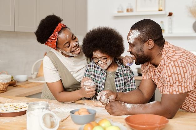 Zabawna młoda trzyosobowa rodzina z mąką na twarzach bawiąca się podczas gotowania domowego ciasta