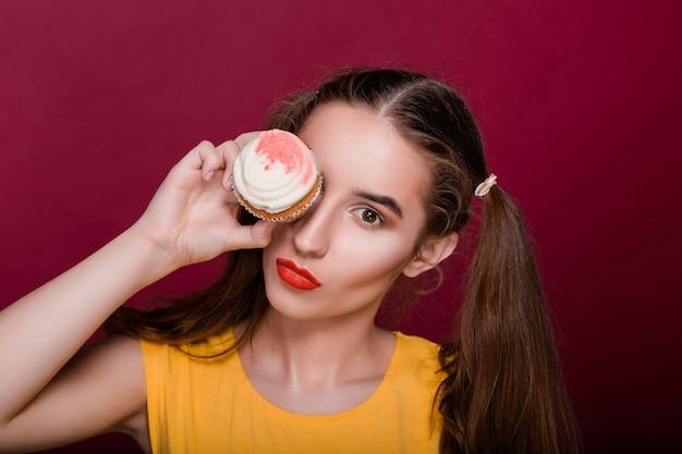 Zabawna modelka brunetka z czerwonymi ustami bawi się z babeczką w dłoni zakrywającą jej oko