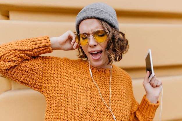 Zabawna modelka z krótkimi kręconymi włosami śpiewa ulubioną piosenkę, stojąc na ulicy ze smartfonem