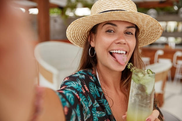 Zabawna modna młoda kobieta pokazuje język, robi selfie z telefonu komórkowego, trzyma w rękach świeży koktajl, lubi rekreację i dobry letni wypoczynek. turystyczna kobieta w przytulnej kawiarni