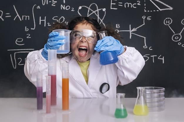 Zabawna naukowiec dziewczyna w fartuchu z kolbami