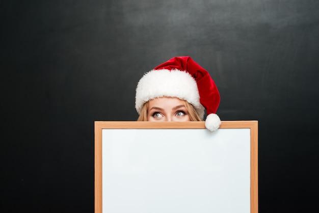 Zabawna nieśmiała dziewczyna w kapeluszu świętego mikołaja chowająca się za pustą białą tablicą