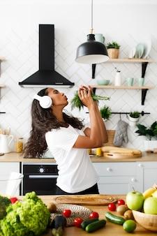 Zabawna oliwkowa kobieta z zamkniętymi oczami w dużych słuchawkach uśmiecha się i udaje emocjonalnie, jakby śpiewała w zieleni w nowoczesnej kuchni