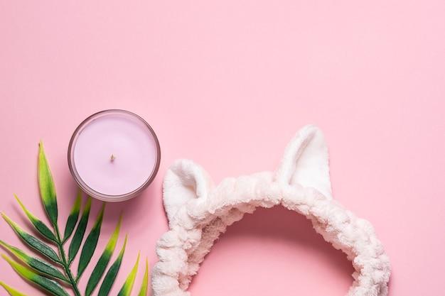 Zabawna opaska zapachowa świeca i liść palmowy na różowym pastelowym tle