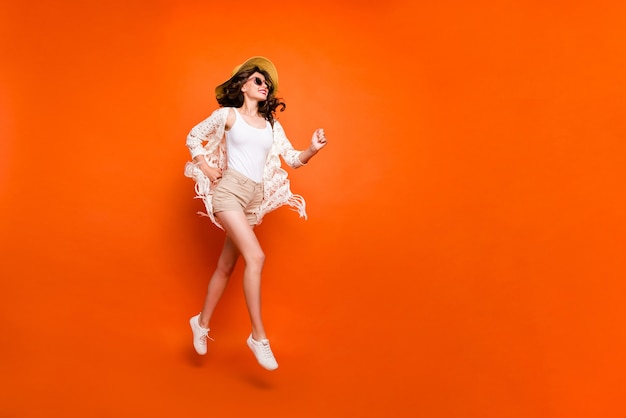 Zabawna pani skacząca wysoko, chodząca, nosić stylową czapkę przeciwsłoneczną vintage stylowe modne szorty peleryna.