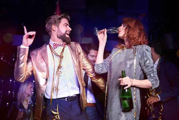 Zabawna para ciesząca się podczas przyjęcia sylwestrowego