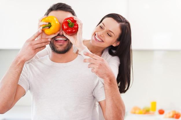 Zabawna para. piękna młoda kobieta zasłaniająca oczy swojego chłopaka kolorową papryką i uśmiechnięta, gdy oboje stoją w kuchni