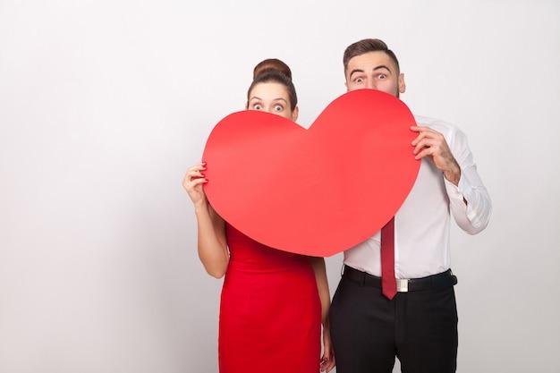 Zabawna para w chowanego za wielkim czerwonym sercem. wewnątrz, studio strzał, na białym tle na szarym tle