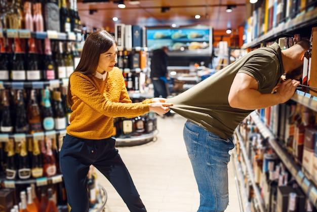 Zabawna para wybiera alkohol w sklepie spożywczym. mężczyzna i kobieta z koszyka kupują napoje na rynku