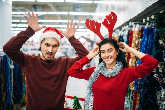 Zabawna para wybiera ozdoby świąteczne w supermarkecie