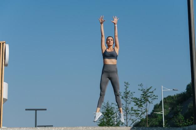 Zabawna piękna brunetka ćwicząca na świeżym powietrzu, skacząca pionowo z prostym ciałem, wyrzucająca ręce w powietrze. w szarym topie i spodniach do jogi. w słoneczny dzień.