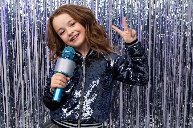 Zabawna piękna gospodarzka trzyma mikrofon w dłoniach i pokazuje klasę przy ścianie błyszczącego blichtru
