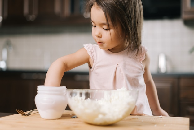 Zabawna piękna mała dziewczynka bierze sól z solniczki palcami, aby dodać ją do ciasta