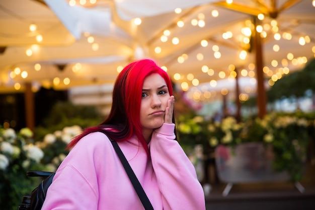 Zabawna piękna rudowłosa dziewczyna wieczorem na oświetlonej ulicy miasta.