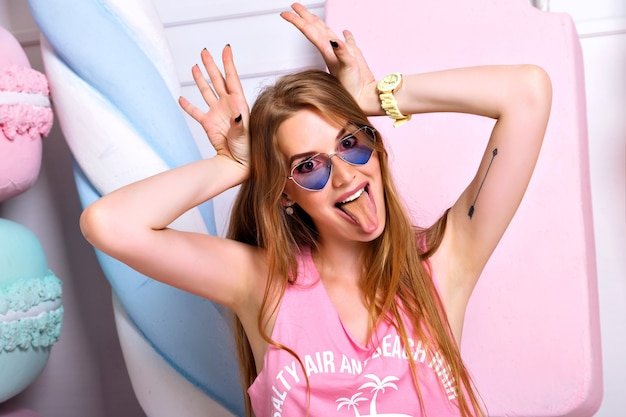 Zabawna piękna szalona kobieta pozuje na ścianie wielkich kolorowych fałszywych słodyczy, robiąc grymas, pokazując język. jasne emocje, modne różowe ubrania, szczęśliwa blondynka