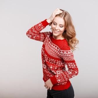 Zabawna piękna szczęśliwa kobieta z uśmiechem w modnym czerwonym swetrze na szarym tle