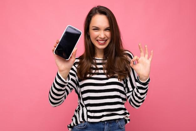 Zabawna piękna szczęśliwa młoda kobieta ubrana w paski sweter na białym tle nad tłem z miejsca na kopię, pokazując ok gest patrząc na aparat pokazujący ekran telefonu komórkowego. makieta, wycinanka