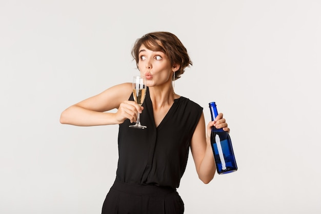 Zabawna pijana kobieta imprezuje, trzymając butelkę i popijając szampana ze szkła, stojąc nad białym.