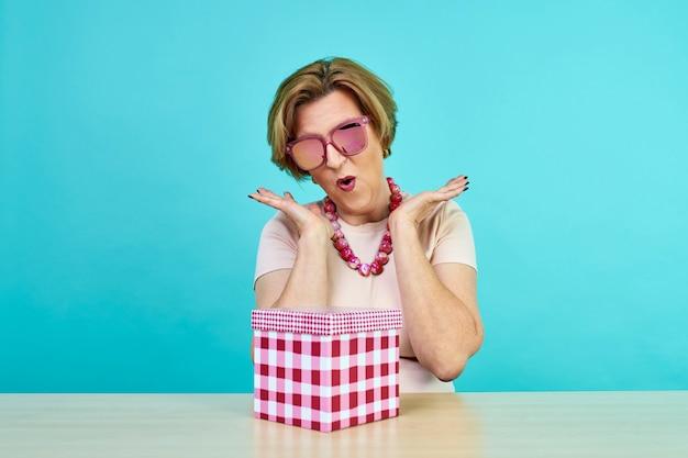 Zabawna podekscytowana stara kobieta. kobieta w wieku bardzo cieszyła się z otrzymywania prezentów. teraźniejszy pudełko odizolowywający nad błękit ścianą