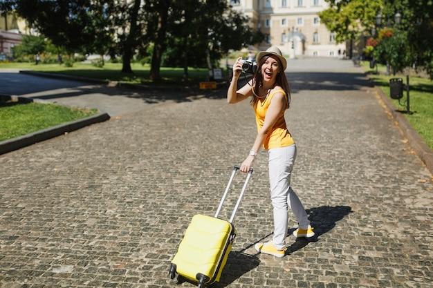 Zabawna podróżnik turystyczna kobieta w żółtych ubraniach z walizką robienia zdjęć na retro aparat fotograficzny vintage spaceru w mieście na świeżym powietrzu. dziewczyna wyjeżdża za granicę na weekendowy wypad. styl życia podróży turystycznej.