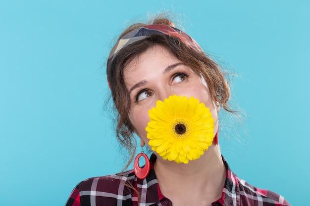 Zabawna pozytywna młoda kobieta w obrazie retro trzyma jasny żółty kwiat gerbera w zębach pozuje na niebieskiej powierzchni