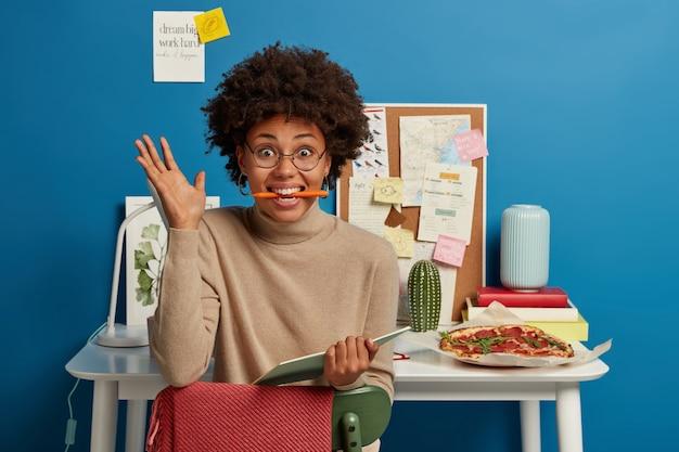 Zabawna, radosna afroamerykanka trzyma w ustach długopis, trzyma otwarty notes, unosi dłoń, nosi okulary