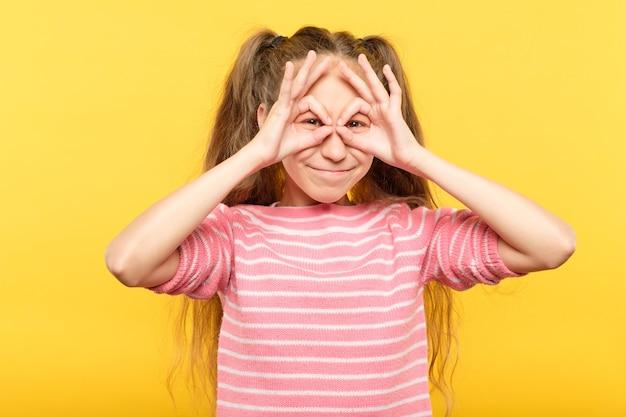 Zabawna, radosna, figlarna dziewczyna udająca, że patrzy przez lornetkę z rąk. emocjonalny wyraz twarzy.