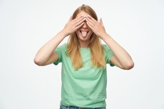 Zabawna radosna kobieta z piegami w miętowej koszulce stożkowatych oczach przez ręce pokazujące język i bawiące się na biało