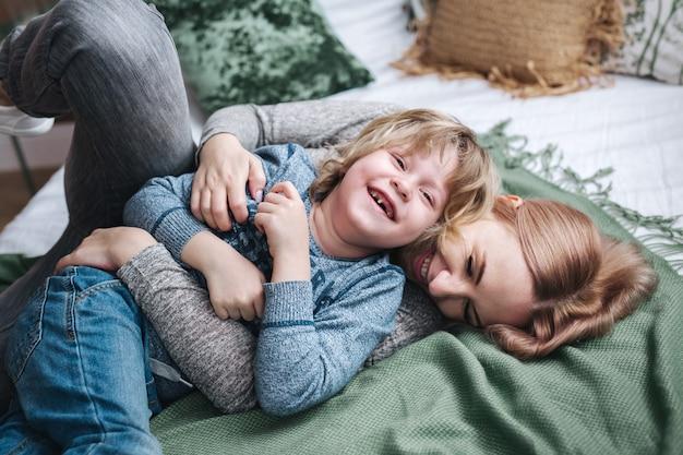 Zabawna rodzina. matka i dziecko syn śmiejąc się w łóżku