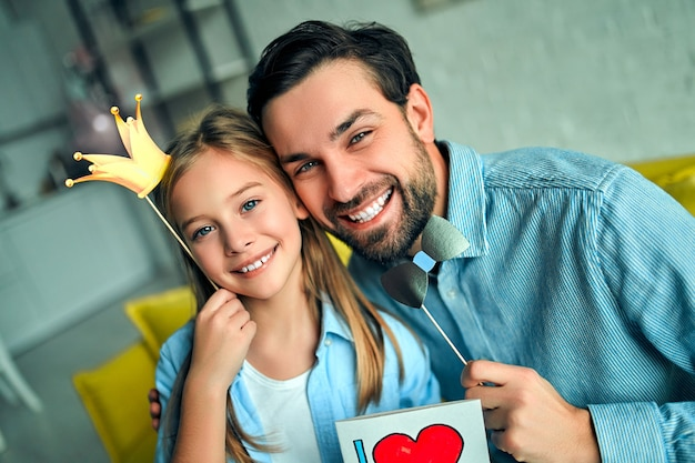 Zabawna rodzina! ojciec i jego córka dziecko z akcesoriami papierowymi. piękna zabawna dziewczyna trzyma papierową koronę na patyku. gratuluje tacie i wręcza mu pocztówkę z okazji dnia szczęśliwego ojca!