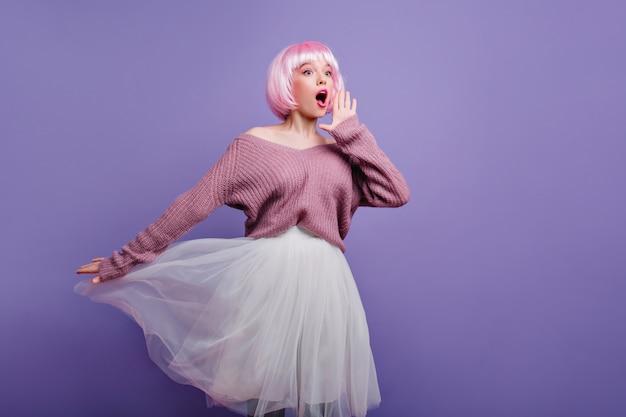 Zabawna różowowłosa dziewczyna w pozie peruka urocza modelka ma na sobie białą spódniczkę i bystry peruke podczas sesji zdjęciowej.
