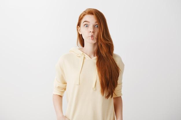 Zabawna ruda dziewczyna ssie usta jak ryba, krzywiąc się
