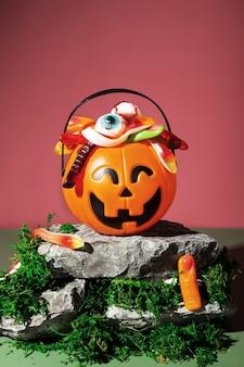 Zabawna sceneria halloween. cukierek albo psikus. pumpkin jack wypełniony różnymi przerażającymi słodyczami stoi na kamieniach i mchu