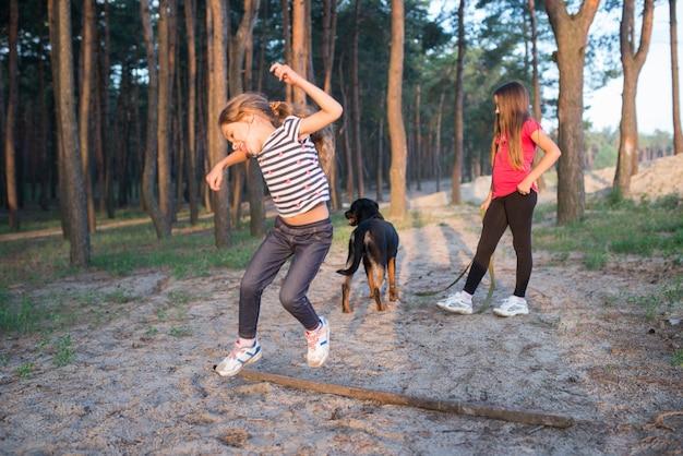 Zabawna śliczna mała dziewczynka skacząc przez dużą starą suchą gałąź z szerokim uśmiechem na twarzy w gęstym lesie sosnowym na ciepły słoneczny letni jasny poranek, a siostra z psem stoi w tle