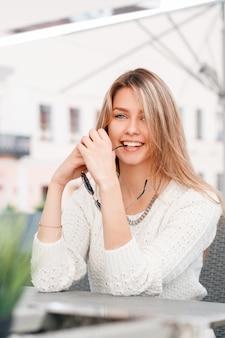 Zabawna śliczna młoda blond kobieta w białym swetrze z dzianiny vintage siedzi przy stole w ulicznej kawiarni. piękna dziewczyna na wakacjach.