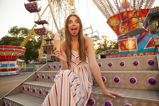 Zabawna śliczna młoda kobieta w letniej sukience pozuje nad diabelskim młynem w wesołym miasteczku, trzymając w dłoni lody i pokazując różowy język