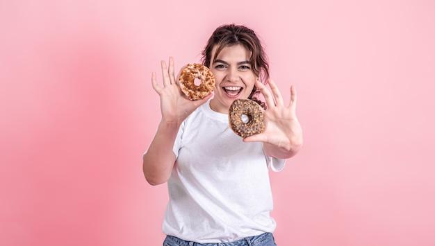 Zabawna śliczna młoda piękna dziewczyna ubrana w białą koszulkę trzyma dwa słodkie pieczone pączki
