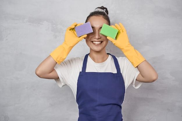 Zabawna sprzątaczka w mundurze i gumowych rękawiczkach zakrywających oczy gąbkami kuchennymi do czyszczenia